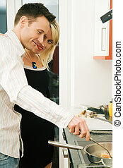 Couple cooking - Young couple in their kitchen at home: She...