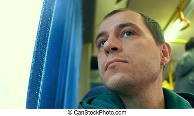 Caucasian man looking through the bus window. Transportation...