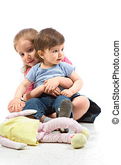 Siblings - brother and sister sitting on floor with doll