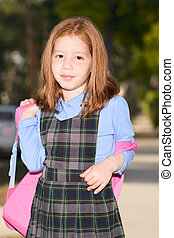 Elementary age schoolgirl in uniform with backpack -...