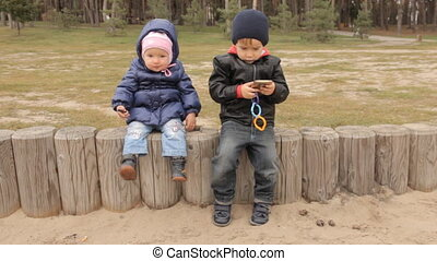 A small boy and a baby girl sitting on a fence the boy pushing buttons in the smartphone. The girl swinging her legs.