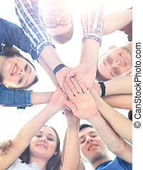 group of smiling teenagers with hands on top of each other