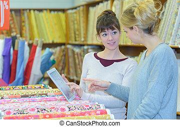 designer choosing fabric at haberdashery