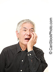 senior Japanese man suffers from toothache - studio shot of...