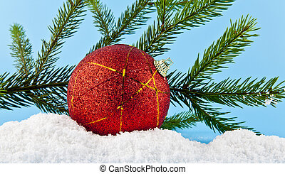 Christmas tree branch, Christmas balls, and white snow on a...