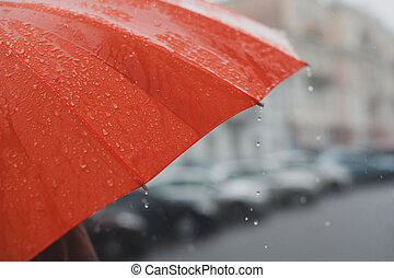Rain on umbrella - rain drops falling from a orange umbrella
