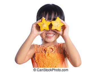Happy Asian Chinese little girl using starfruit as glasses