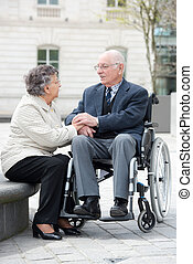 old man in wheelchair with wife outdoors