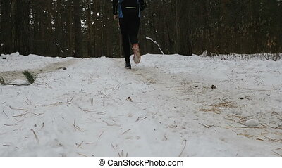 male runner running winter forest, snow spray from under...