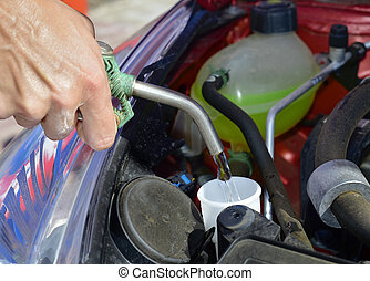 filling the tank of windshield washer fluid - closeup of a...