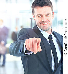 Portrait of smiling mature business man pointing at you in office