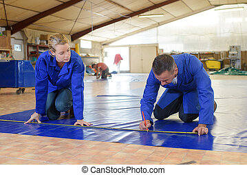 Two workers measuring material on floor