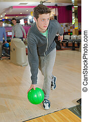 Young man poised to throw bowling ball