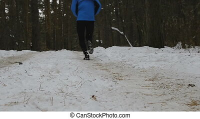 male runner running winter marathon, snow spray from under...