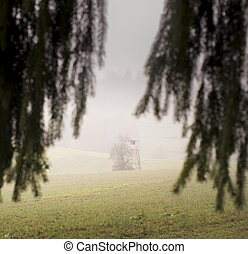 Wooden hunting lodge in the field, surrounded with fog.