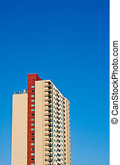 Beige and Red Condo Tower Rising into Blue Sky