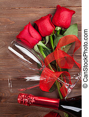 Red roses and champagne over wooden background. Top view