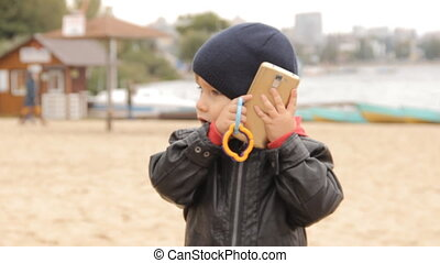 A little boy pushing buttons in the smartphone, answers the...