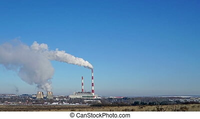 Thermal power plant or a factory with Smoking chimneys on the horizon. Polluting smoke into the clear blue sky.