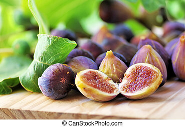 Ripe figs with green leaves on table