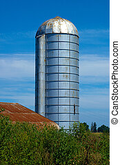 Silo with barn and blue sky on warm sunny day