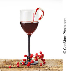 wine glass with candycane and holly wood table with white...