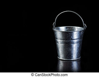 Metal bucket on black with copy spa