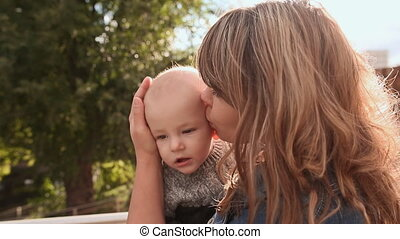 Young beautiful mother holding a baby in her arms. Mother hugging and kissing her son on the nature.