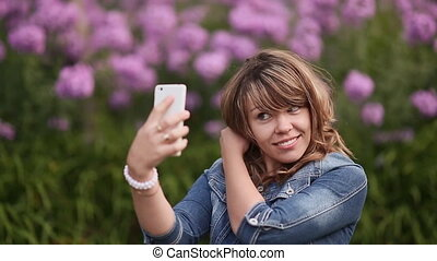 A young girl takes pictures on your phone, selfi among the flowers.