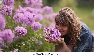 Young girl enjoys the smell of flowers on the walk. - Young...