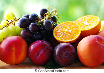 ripe sliced oranges, grappes, peaches and plums