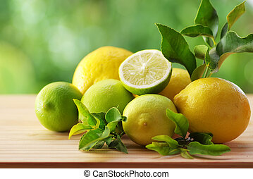 Fresh ripe citruses with leaves on wood table