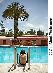 Young Boy Enjoying Vacation at Tropical Swimming Pool in...