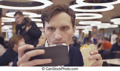 Young men using smartphone eat Shawarma roll at food court...