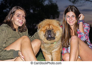 Girls petting a dog in a park at dusk. They are sitting enjoying the evening. The dog looks like a furry teddy bear.