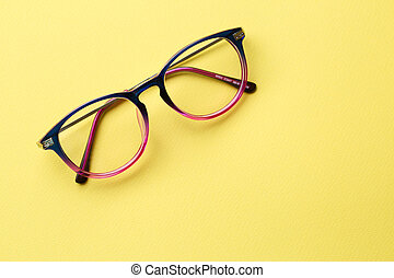 Blue-pink glasses with clear lenses on yellow background...