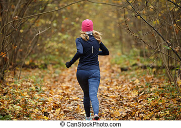 Young sportswoman in autumn forest among yellow leaves