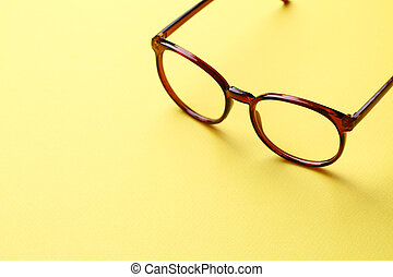Brown glasses on yellow background - Brown glasses with...