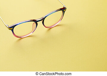 Blue-pink glasses on yellow space - Blue-pink glasses with...