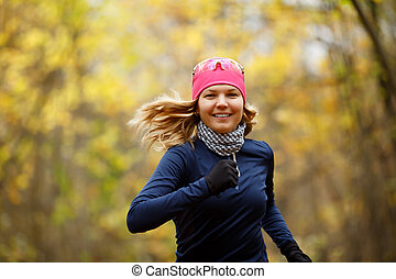 Happy girl with flowing hair runs in autumn park
