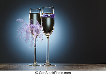 Champagne glasses decorated purple bow-tie and veil for honeymooners