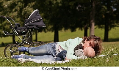 Happy young mother plays with the baby on the lawn, kissing...