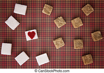 White and brown sugar cubes with a red heart on one of them....