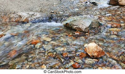 Clear water runs between the stones. Valley Issyk-Ata,...