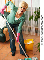 Woman mopping the floor - Woman cleaning and mopping the...