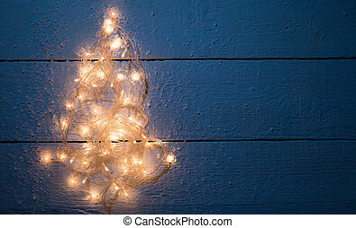 Christmas card with luminous garland on empty wooden...