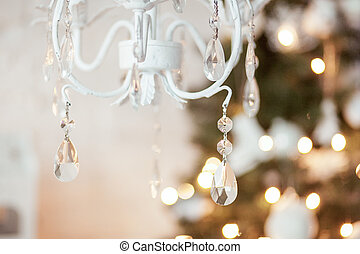 elegant chandelier in the background Christmas decorations, garlands, xmas tree. interior in white and gold colors