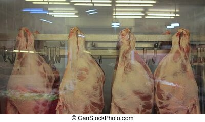 animal carcasses in the meat department of a supermarket.