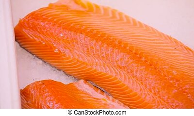 salmon fillets on ice in supermarket.