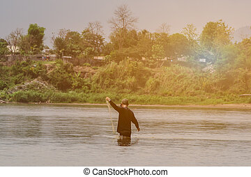 Back view of Asian fisherman throwing fish net to catch fish...